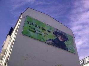 Bild einer Soldatin mit Gefechtshelm und getarntem Gesicht. Daneben der Spruch Schön Bund, mit d statt t geschrieben, und der Zeile Soldatin in der Bundeswehr